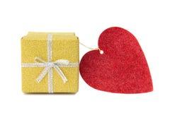 Den guld- gåvaasken och röd hjärta formade kortet Royaltyfri Foto