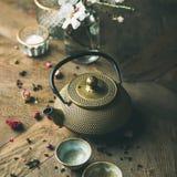 Den guld- järntekannan, koppar, den torkade rosen, stearinljus, mandel blommar Arkivfoton