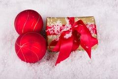 Den guld- julgåvan med röd jul klumpa ihop sig i snön Arkivfoto