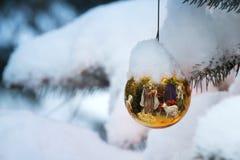Den guld- julgranprydnaden reflekterar julkrubban Arkivfoton