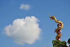 Den guld- kinesiska drakestatyn rullar över polen och stor molnbakgrund Fotografering för Bildbyråer