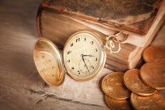 Den guld- klockan och vi dollar myntar en bok Royaltyfria Foton