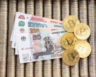 Den guld- kryptan myntar bitcoin BTC, papper av ryska rubel Metallmynt läggas ut i slät bakgrund, närbildsikt f Royaltyfri Foto