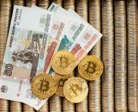 Den guld- kryptan myntar bitcoin BTC, pappers- valörer av ryska rubel Metallmynt läggas ut i slät bakgrund, c Arkivfoton