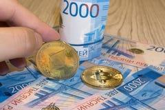 Den guld- kryptoen myntar bitcoin BTC, pappersanmärkningar av ryska rubel Metallmynt läggas ut i en bakgrund till varandra, närbi Royaltyfri Foto