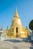 Den guld- pagoden i Wat Pra Kaew, den storslagna slotten, blå himmel, T Royaltyfri Foto