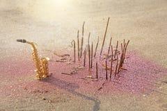 Den guld- saxofonalten står på sanden bredvid det doftande och rosa färgerna som skiner Romantisk musikalisk bakgrund Musikalisk  arkivfoto