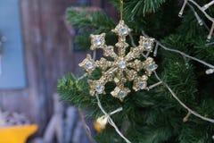 den guld- skinande julprydnaden som hänger från ett grönt, sörjer trädet Arkivbild