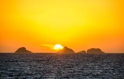 Den guld- solnedgången med den stora runda solen, orange vidsträckt himmel, mörkt vatten av Atlantic Ocean och konturer av berg p royaltyfri foto