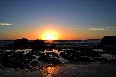 Den guld- solnedgången på en strand med vaggar och vaggar tips Arkivfoton