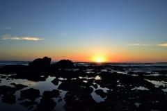 Den guld- solnedgången på en strand med vaggar och vaggar tips Royaltyfri Bild