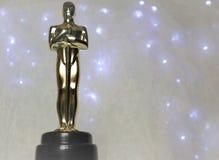 Den guld- statyn av Oscar på en vit bakgrund arkivfoto