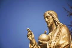Den guld- statyn Jesus Christ He rymmer sfären med ett kors som ett symbol av förvaltarskapet av kristendomen ovanför jorden royaltyfri fotografi