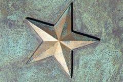 Den guld- stjärnan på rostigt belägger med metall bakgrund Royaltyfria Bilder