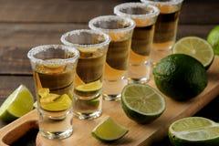 Den guld- tequilaen i ett skjutit exponeringsglas för exponeringsglas med saltar och kalkar på en brun träbakgrund stång alkoholi arkivfoto
