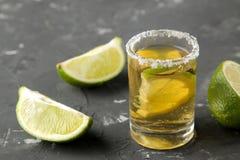 Den guld- tequilaen i ett skjutit exponeringsglas för exponeringsglas med saltar och kalkar slut upp på en svart konkret bakgrund arkivfoto