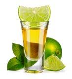 Den guld- tequilaen sköt med limefrukt som isolerades på vit arkivfoton