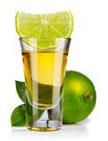 Den guld- tequilaen sköt med limefrukt som isolerades på vit royaltyfria foton