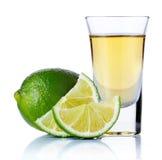 Den guld- tequilaen sköt med limefrukt som isolerades på vit Royaltyfri Fotografi
