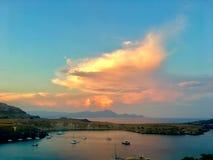 Den guld- timmen av himmel över lindos skäller, och många yachter i havet tycker om aftonen royaltyfri foto
