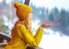 Den gulliga älskvärda flickan i en luva och den hållande tröjan gömma i handflatan ut av handen under fallande snö utanför staden Arkivfoto