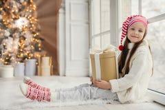 Den gulliga älskvärda flickan med gåva, sitter nära fönster i vardagsrum, ser delightfully in i kamera, beundrar underbara härlig arkivfoton