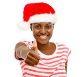 Den gulliga afrikansk amerikanflickan fingrar tummar upp bärande Kristus för tecken Arkivfoto