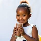 Den gulliga afrikanska flickan med mjölkar chokladdrinken Arkivbilder