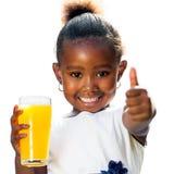 Den gulliga afrikanska flickan som gör tummar, up hållande orange fruktsaft Fotografering för Bildbyråer