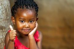 Den gulliga afrikanska flickavisningen tummar upp. Royaltyfria Bilder