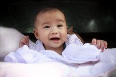 Den gulliga asiatet behandla som ett barn att le vänder mot legat på säng arkivfoto