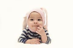 Den gulliga asiatet behandla som ett barn flickan med rosa färgkaninhatten på vit bakgrund Arkivbild