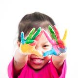 Den gulliga asiatiska barnflickan med händer målade i färgrik målarfärg Royaltyfri Bild