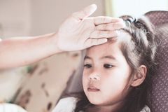 Den gulliga asiatiska barnflickasjukdomen och moderhanden trycker på hennes panna royaltyfria bilder