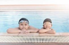 Den gulliga asiatiska flicka- och fettpojken ler i simning Arkivfoton