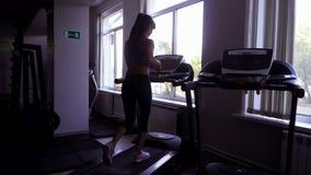Den gulliga asiatiska flickan är förlovad i kondition running treadmill stock video