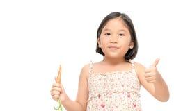 Den gulliga asiatiska flickan som behandla som ett barn moroten som isoleras på vit bakgrund Arkivfoton
