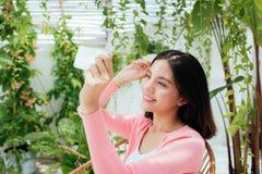 Den gulliga asiatiska flickan tar selfiefoto och sitter i solig gar Arkivbilder