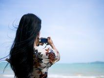 Den gulliga asiatiska kvinnan som bär retro klänninganseende på den hållande kameran för sjösidan i hand och, tar ett foto royaltyfri fotografi