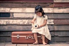 Den gulliga asiatiska lilla flickan sitter på resväskan Royaltyfri Fotografi