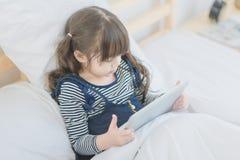 Den gulliga asiatiska lilla flickan tycker om att hålla ögonen på tecknade filmen på den smarta minnestavlan Arkivbild