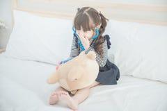 Den gulliga asiatiska lilla flickan tycker om att spela doktorn med doktorsleksakuppsättningen Royaltyfri Bild