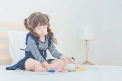 Den gulliga asiatiska lilla flickan tycker om att spela med leksakuppsättningen Arkivbild