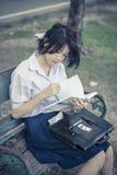 Den gulliga asiatiska thailändska skolflickastudenten i högstadiumlikformig är sitter Arkivfoto