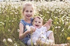 Den gulliga barnflickan på kamomillfälttusenskönan med behandla som ett barn brodern royaltyfri fotografi