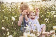 Den gulliga barnflickan på kamomillfälttusenskönan med behandla som ett barn brodern arkivfoto