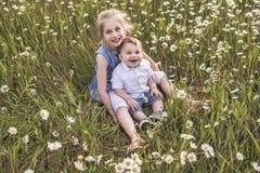 Den gulliga barnflickan på kamomillfälttusenskönan med behandla som ett barn brodern arkivbilder