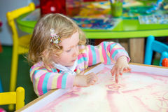 Den gulliga barnflickateckningen drar framkallande sand i förträning på tabellen i dagis Arkivfoton