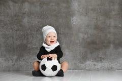Den gulliga bilden av behandla som ett barn rymma en fotbollboll arkivfoto