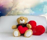 Den gulliga björndockan sitter med röd hjärta i drömlik söt regnbågehimmel Arkivfoto